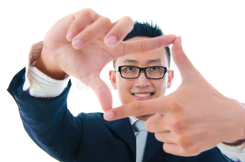 Fingerrahmen. Lächelnder asiatischer Geschäftsmann, der einen Rahmen mit Flosse macht stockbilder