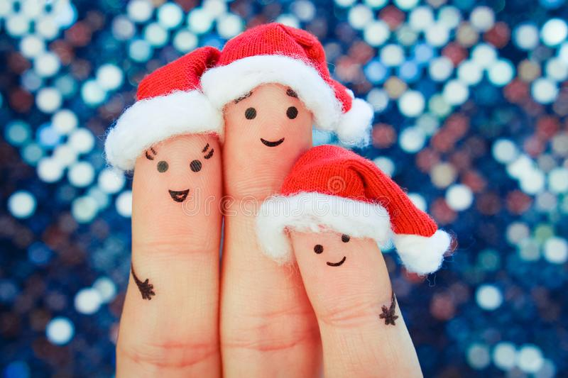 Fingers art of family celebrates Christmas. Concept of group of people smiling in new year hats. royalty free stock images