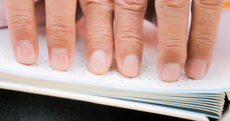 Fingers Of Blind Man Touching Page On Braille Book. Hispanic blind man, people with disability, handicapped person and everyday life. Visually impaired man royalty free stock photography