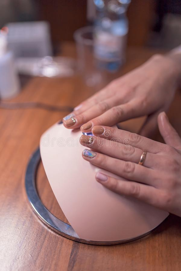 Fingers of both hands varnish on the lamp for manicure stock photos