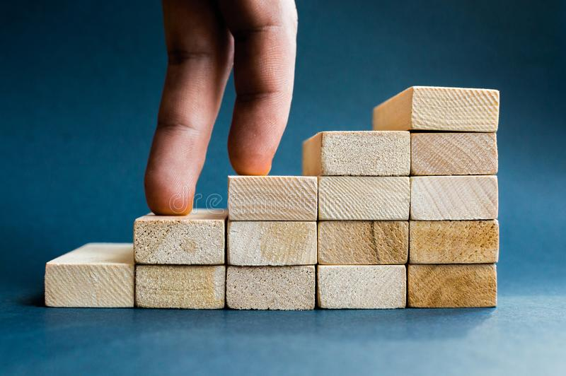 Fingers climbing the stairs made with wooden blocks. Concept of the success, career, goal achievement, hardworking. stock image