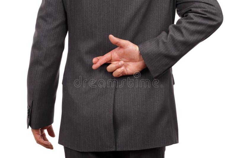 Fingers crossed behind businessmans back stock image