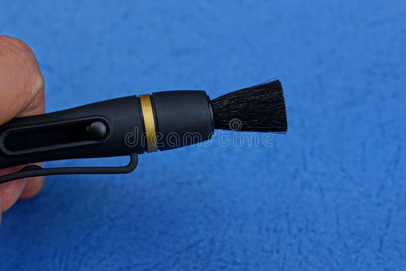 Fingers hold black cleaning pencil with a brush royalty free stock image