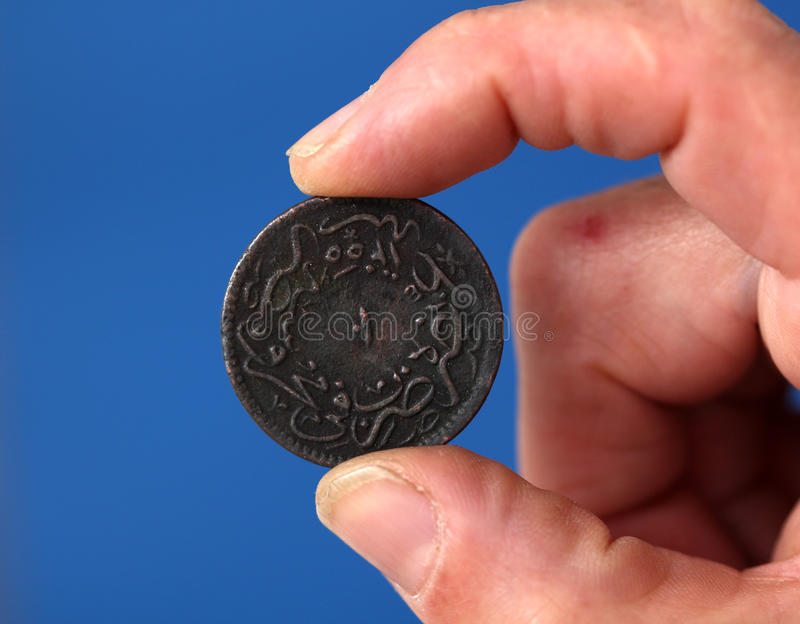 Fingers hold old coin from Ottoman empire stock photo