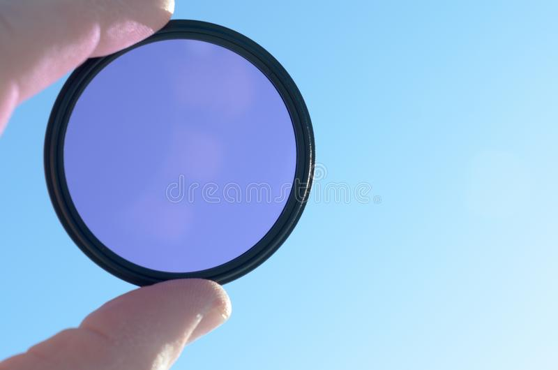 Fingers hold the photo filter against the blue sky. Fingers hold the photo filter against the blue sky stock image