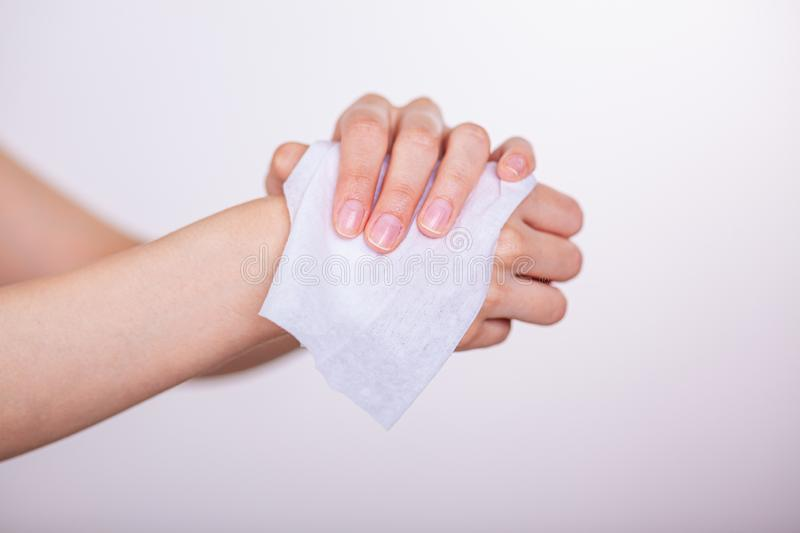 Fingers hold wet wipes and cleaning hands. White background, studio shot stock image