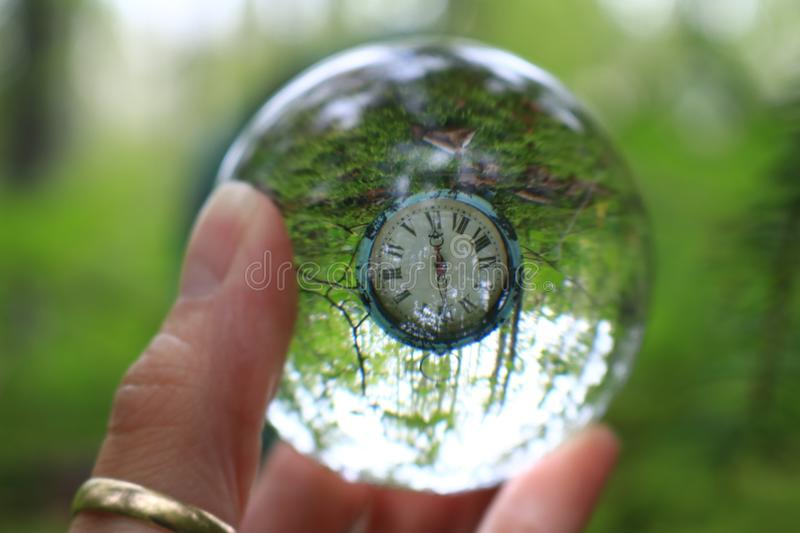 Transparent glass ball reflecting a clock in the forest. Fingers holding transparent glass ball reflecting an antique clock in the forest stock images