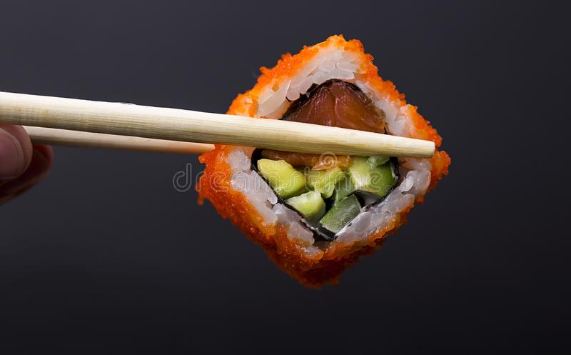 Fingers holding wooden sticks Ð¡alifornia roll stock images