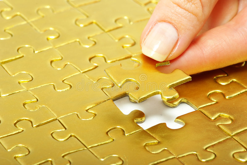 Fingers holdings pazles. Woman fingers holdings gold pazles stock image