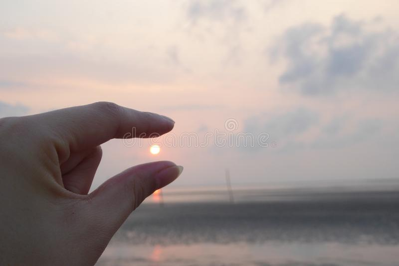 Fingers pinching rising sun. Near the beach at can gio vietnam royalty free stock images