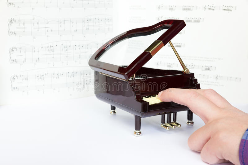 Fingers playing on small model of grand piano. Fingers playing on little model of grand piano. In background music notes on paper stock images