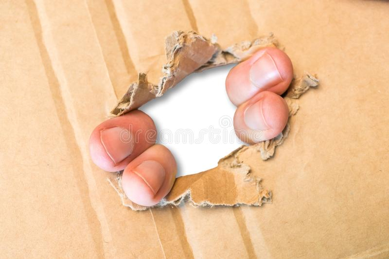 Fingers tear hole in cardboard paper. Frame of torn hole with fingers in cardboard paper stock image