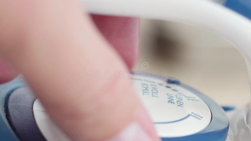 Fingers turning the temperature regulator of iron stock image