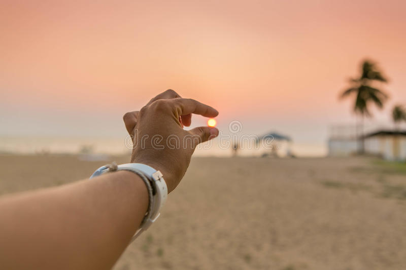 Fingers of woman catching the sun on sunset. stock photo