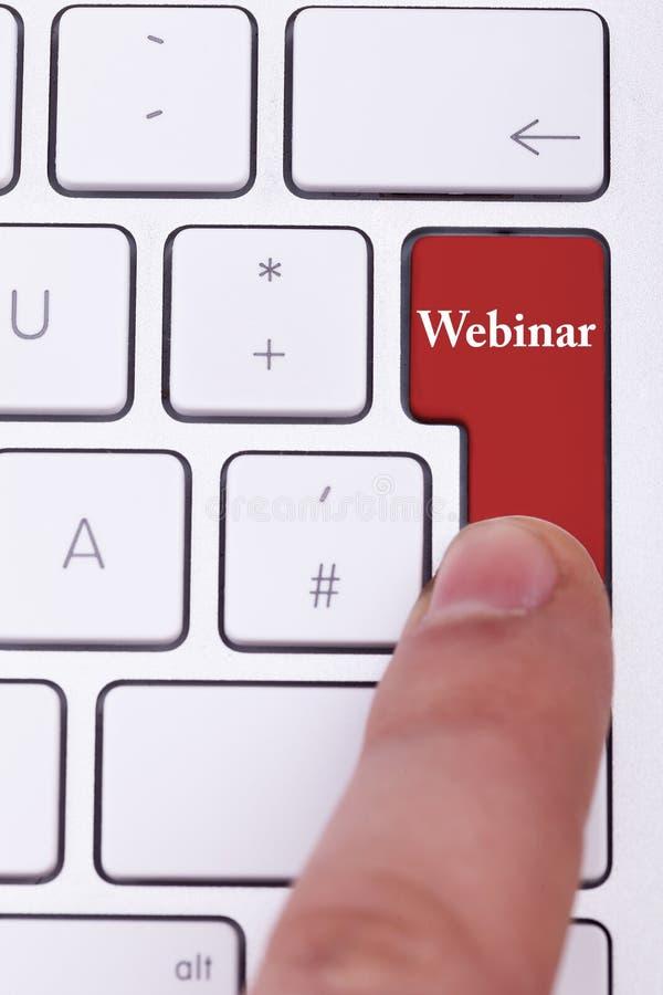 Fingra att trycka på på den röda webinar knappen på det metalliska tangentbordet arkivbild