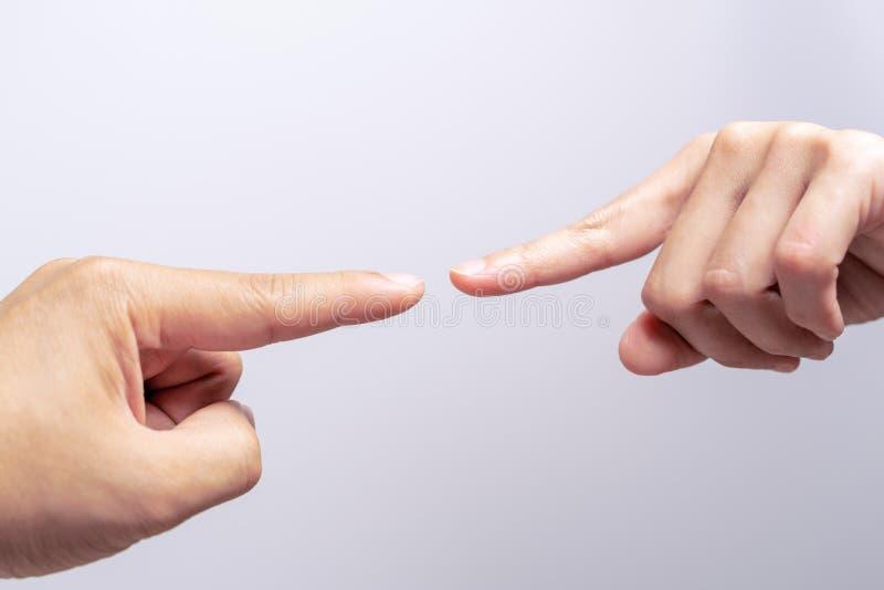 Fingra rörande män för punkt och kvinnahänder som når in mot de och nästan att trycka på Mångfalddifferensbegrepp royaltyfri foto