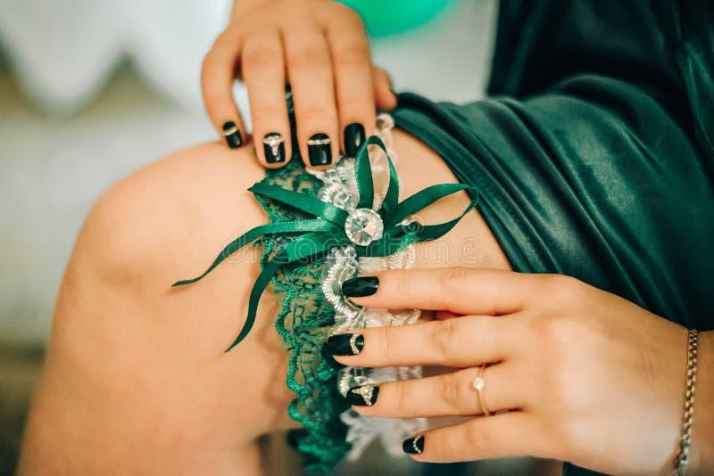 Fingrar av bruden, med en härlig manikyr, uppehälle på hennes ben en bröllopstrumpeband arkivbilder