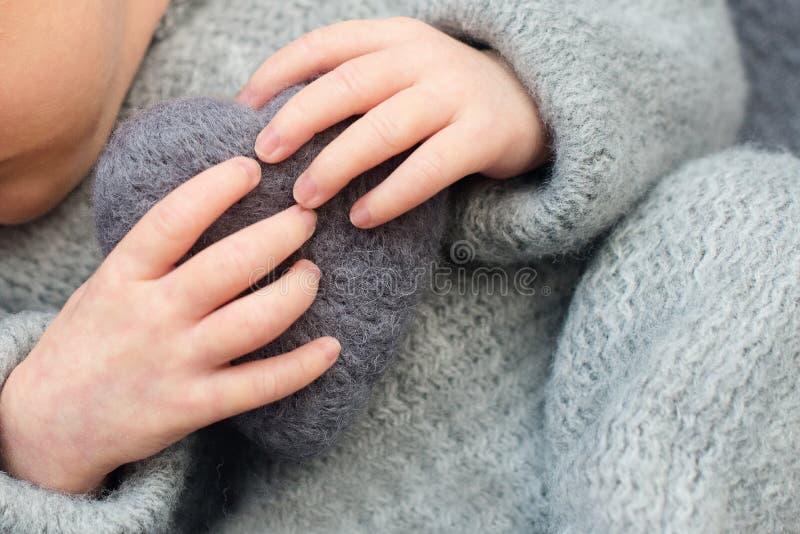 Fingrar av ett nyfött behandla som ett barn, hjärta i händerna av mamman och farsan, händer och spikar av ett barn, de första dag royaltyfria bilder