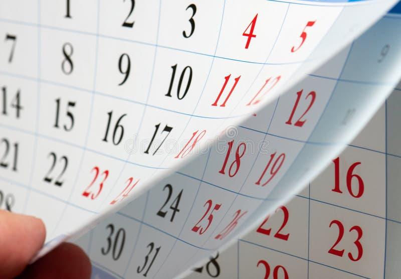 Fingrar rymmer kalenderarket royaltyfria foton