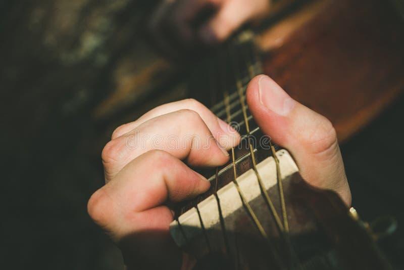 Fingrar som bildar ett ackord på en gitarrfingerboard Manlig hand som spelar på gitarren Selektivt fokusera royaltyfri fotografi