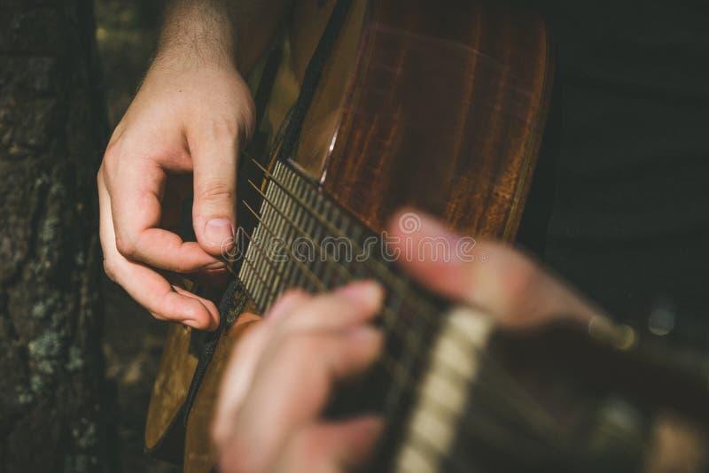 Fingrar som bildar ett ackord på en gitarrfingerboard Manliga händer som spelar på gitarren Selektivt fokusera royaltyfri fotografi