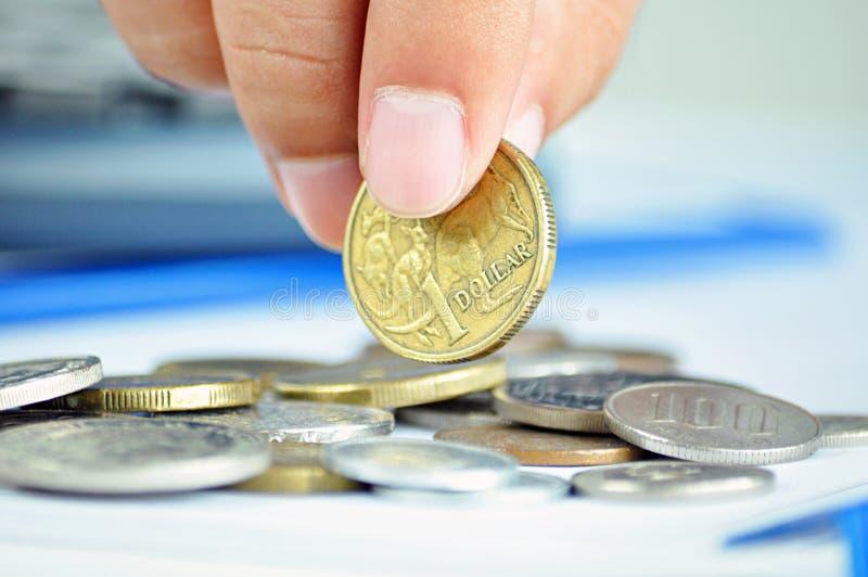 Fingrar som upp väljer ett mynt - en australisk dollar (AUD) royaltyfria bilder