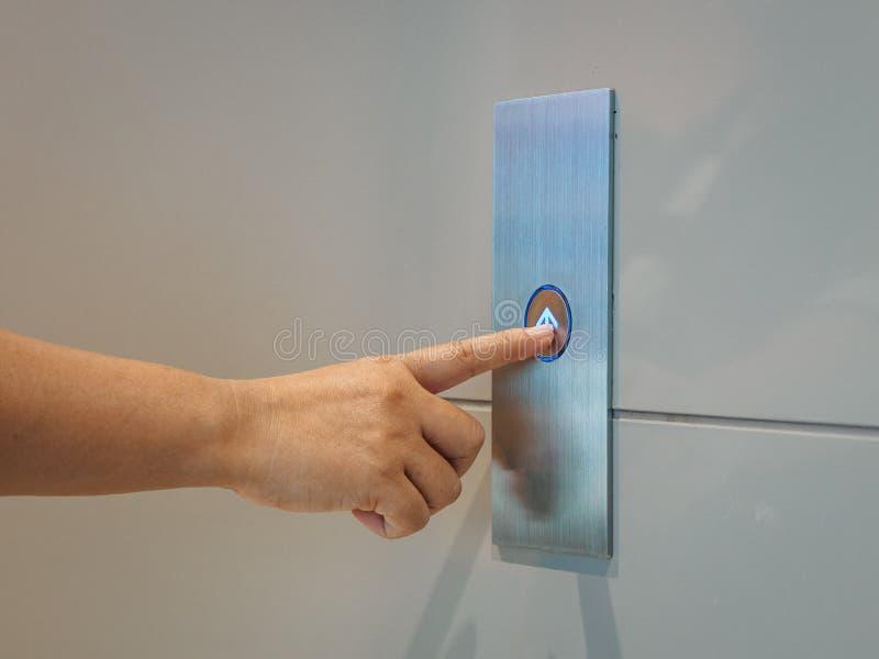 Fingret trycker på hissknappen, uppåt- och neråt knappen kvinnapres arkivbild