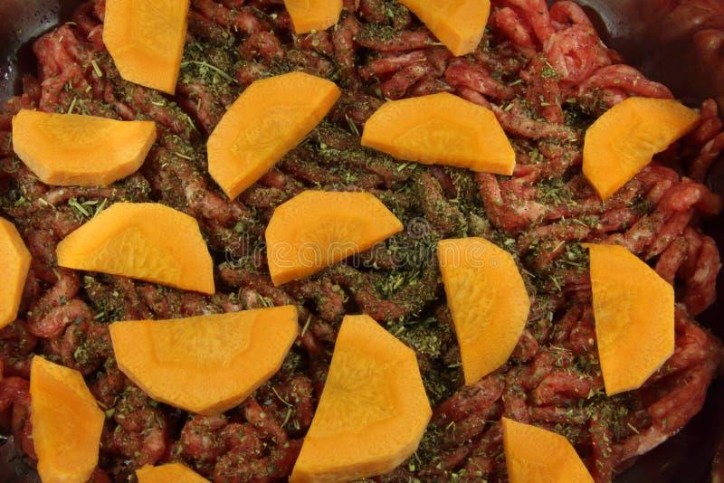 Finhackade nytt kött, orange morötter och Provencal örter Kött, grönsaker och örter, innan att laga mat royaltyfria foton