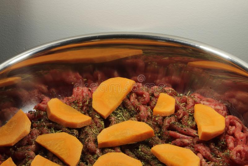 Finhackade nytt kött, orange morötter och Provencal örter i en kastrull Kött, grönsaker och örter i en panna, innan att laga mat royaltyfri bild