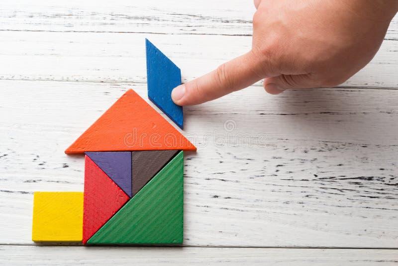 Finir le dernier peu du tangram en bois dans la forme de maison photos stock