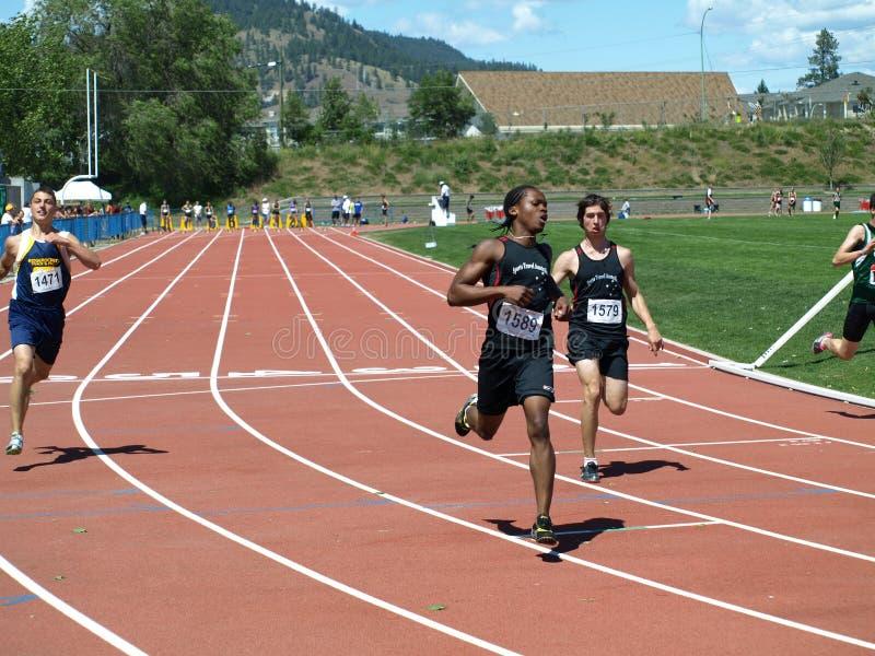 Finish of the 100 meters dash. KELOWNA, CANADA - Brain Michael, Njemanze Adika, Cifra Stefan, Boys 15 Year Olds on the finish of 100 Meter Dash Finals on 27th stock images