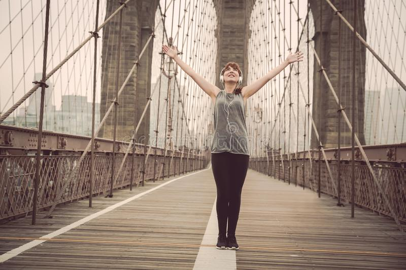Finish my running. Woman on the Brooklyn bridge with arms raised stock image