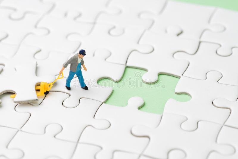 Finish the work project or business success strategy metaphor, miniature people figurine using the forklift to complete the last. White jigsaw puzzle piece on royalty free stock photo
