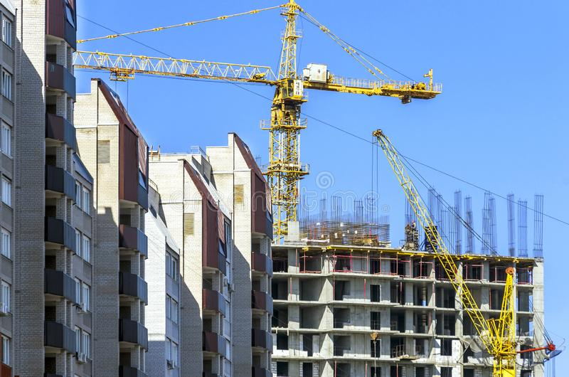 Finished Apartment Building and a New High-Rise Building Construction Site with Yellow Cranes against Blue Sky. Real Estate, stock photo