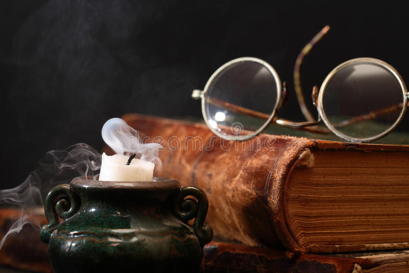Finished Old Book Reading. Vintage still life. Spectacles on closed book near extinguished candle stock photos
