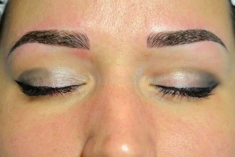 The finished result of microblading, dark eyebrows, permanent makeup on the eyebrows. The finished result of microblading, dark eyebrows, permanent makeup on stock photo