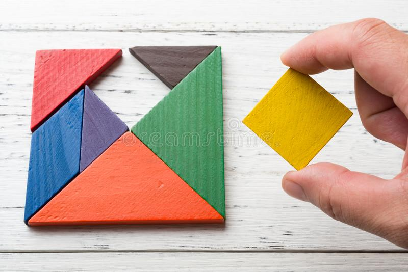 Finishing the last bit of a wooden tangram stock image