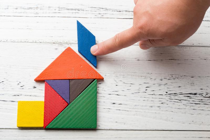 Finishing the last bit of wooden tangram in house shape stock photos