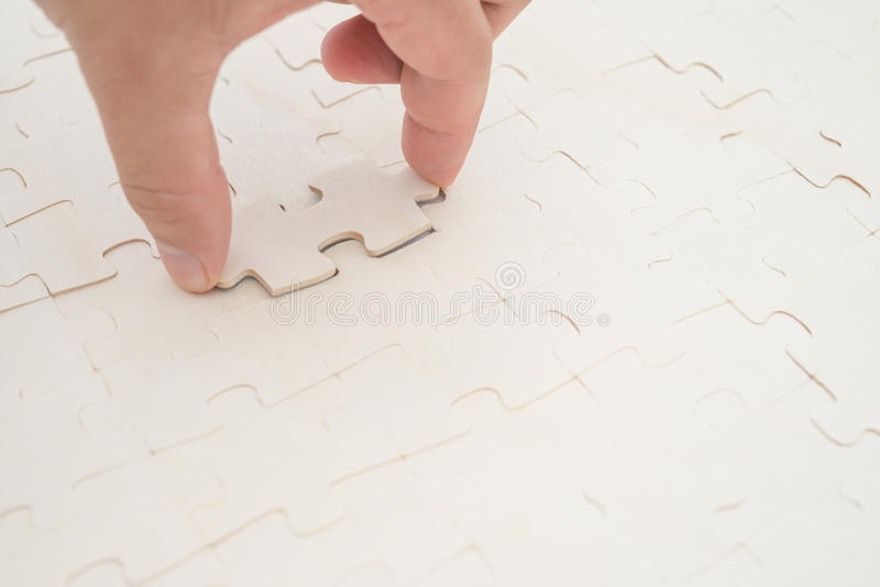 Finishing the last piece of a jigsaw puzzle stock photos