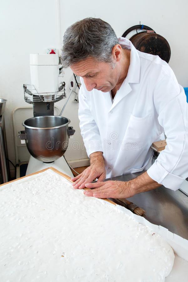 Finishing of nougat specialty by pastry cook in industrial kitchen. Edible rice paper making of Italian white dough with roasted almonds for French sweet nougat royalty free stock image