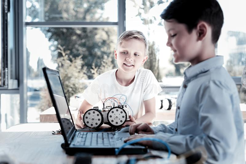 Relaxed children programming their robotic vehicle. Finishing touches. Selective focus on a blond boy with a robotic machine in his hand talking to his mate royalty free stock photo