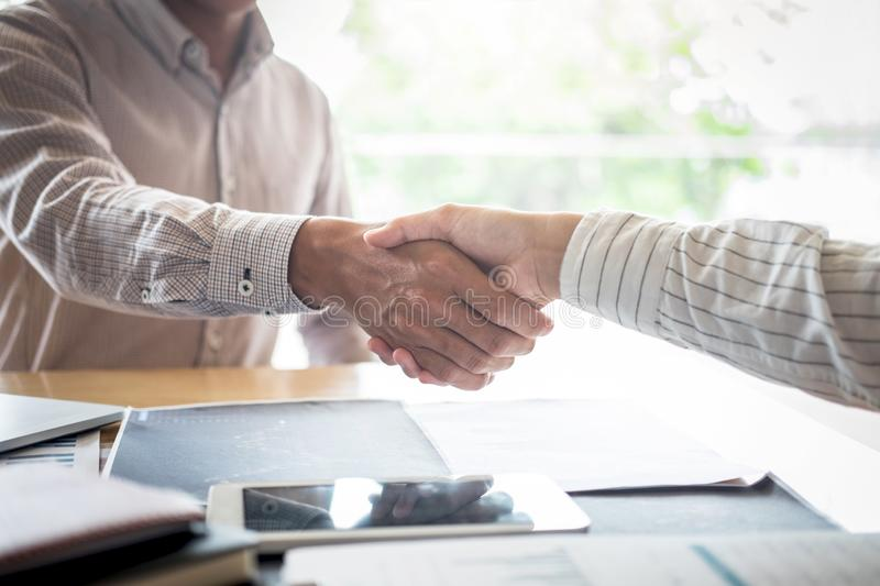 Finishing up a meeting, handshake of two happy business people after contract agreement to become a partner, collaborative stock image
