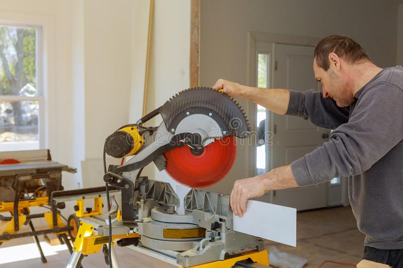 Finishing work the worker cuts the wood moldings baseboard on the miter saw. Finishing work the worker cuts wood moldings baseboard on the miter saw stock photo