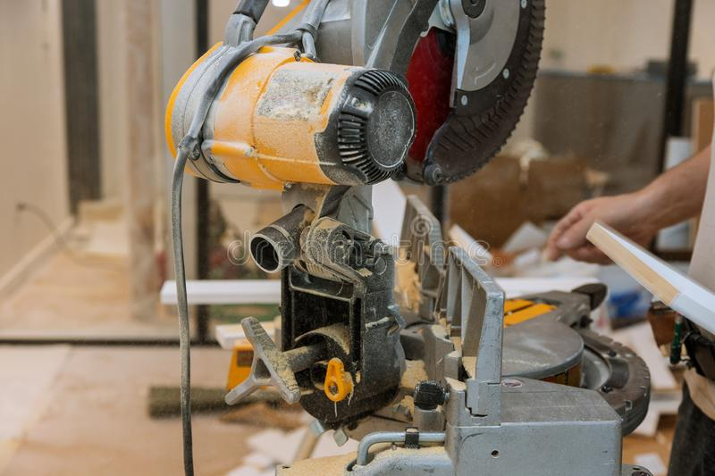 Worker cuts the wood moldings baseboard on the miter saw. Finishing work the worker cuts wood moldings baseboard on the miter saw, sawing, cutting, construction stock photo