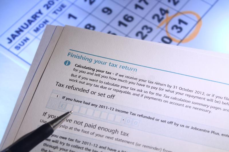 Finishing Your Tax Return. Finish your tax return by 31st January for UK self assessment. Form and calendar reinforcing the date stock photos