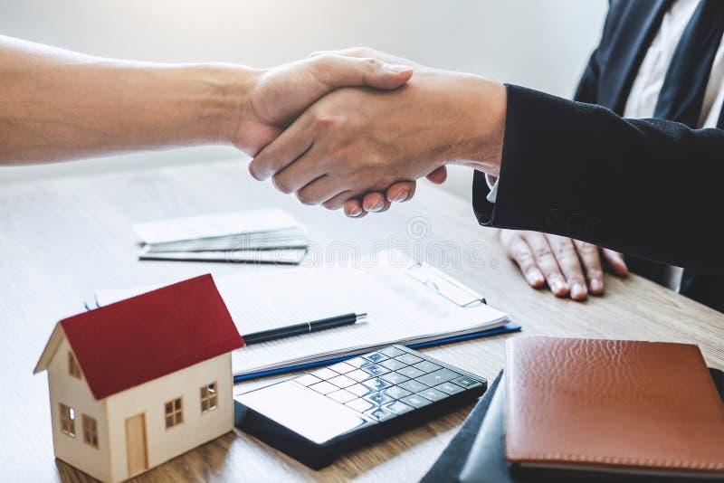 Finissant à l'affaire réussie des immobiliers, du courtier et du client se serrant la main après la signature du formulaire de de photos libres de droits