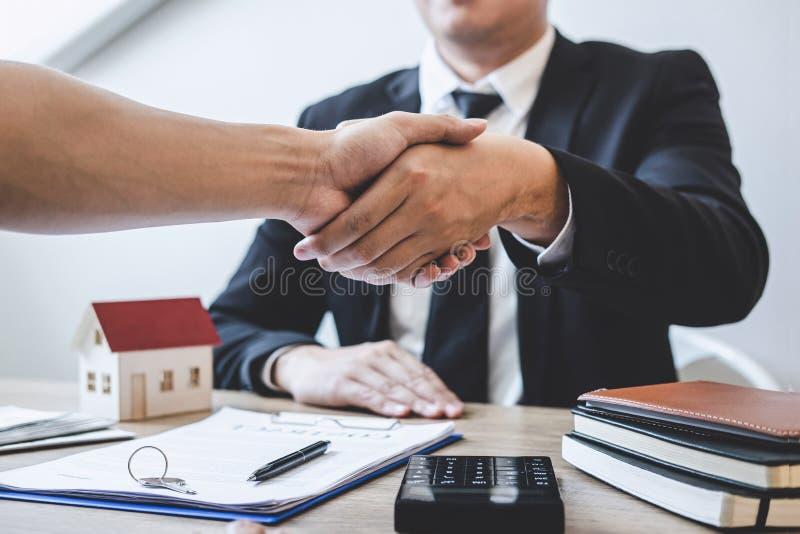 Finissant à l'affaire réussie des immobiliers, du courtier et du client se serrant la main après la signature du formulaire de de photographie stock
