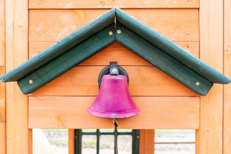 Finja la campana de escuela rosada en un patio de madera al aire libre, con una secuencia para hacer el ruido de Dong del tilín,  imagen de archivo libre de regalías