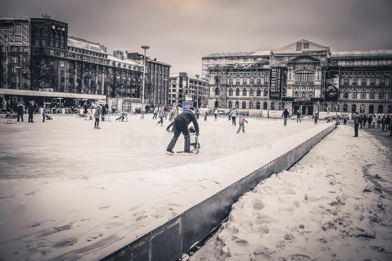 FINLAND, HELSINKI– JANUARY 04, 2015: Skating rink - Railway Square. FINLAND, HELSINKI– JANUARY 04, 2015: Skating rink in front of the building stock image