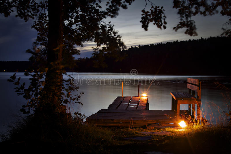 Finland: Lake and sauna experience. Calm lake in the late evening with a platform illuminated with candles. Swimming from sauna on the lakeshore while there is royalty free stock images